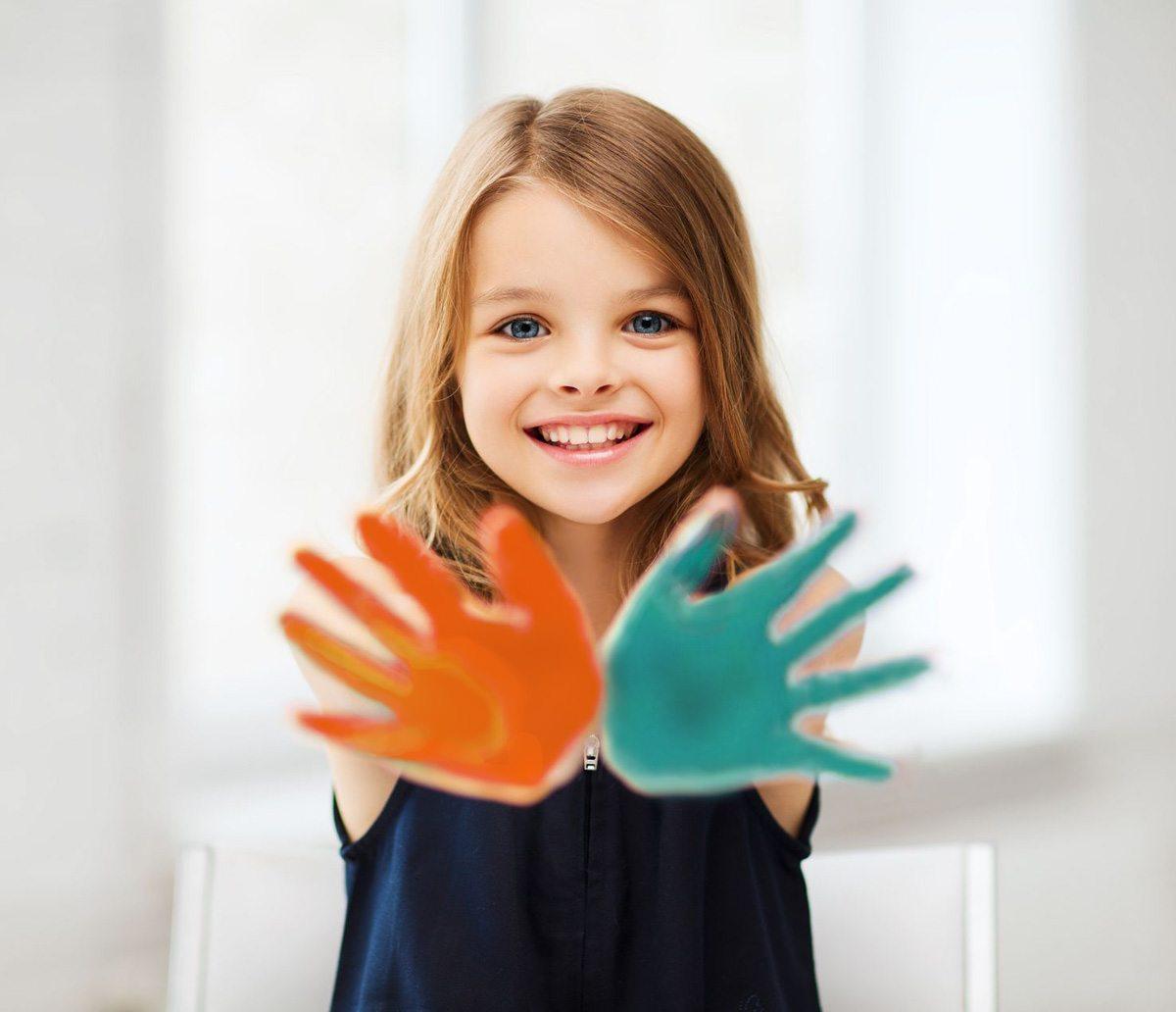 Fillette avec les mains colorées de peinture